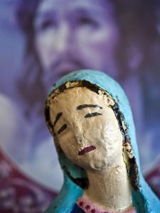 Folk Statue of Our Lady of Guadalupe with Image of Jesus Christ in Background by Ray Laskowitz