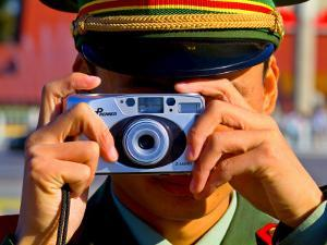 Guard Using His Camera on China's National Day in Tianamen Square, by Ray Laskowitz
