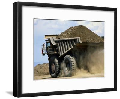A Dump Truck Carrying Gravel Kicks up a Cloud of Dust
