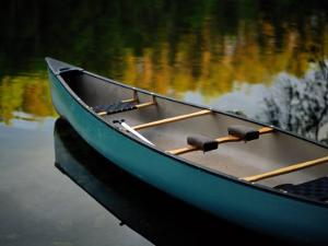 Canoe and Reflections on a Still Lake by Raymond Gehman