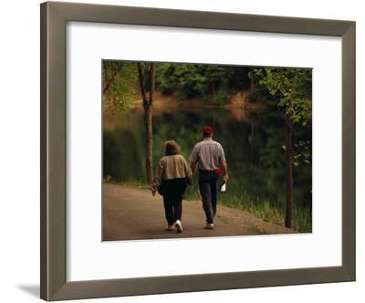 Couple Walking by the Water Along a Park Road