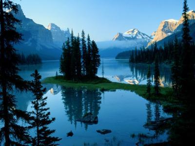 Scenic View of the Lake Surrounded by Evergreens and Snow-Capped Mountains