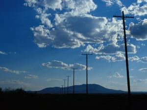 Silhouetted Telephone Poles under Puffy Clouds by Raymond Gehman