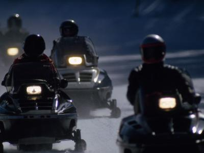 Snowmobilers Ride Down a Snowy Road in Yellowstone Park by Raymond Gehman