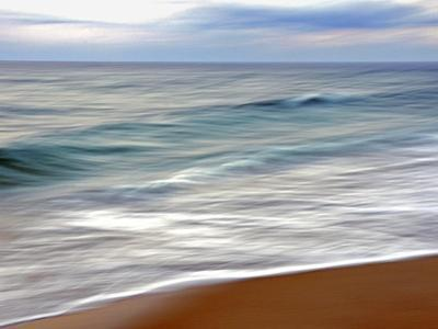 Teal and White Surf Flows on a Rust-Colored Beach under Blue Clouds