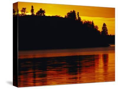 The Setting Sun Casts an Orange Glow Over Manitoba's White Lake