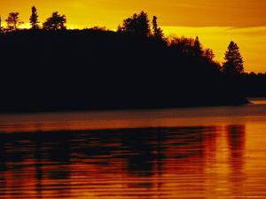 The Setting Sun Casts an Orange Glow Over Manitoba's White Lake by Raymond Gehman