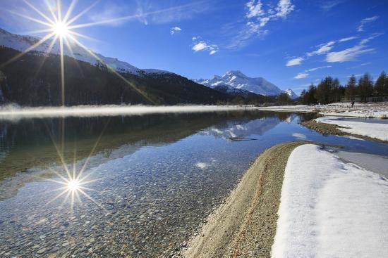 Rays of winter sun illuminate Lake Silvaplana still partially frozen Maloja Engadine Graubunden Can-ClickAlps-Photographic Print