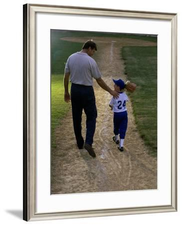 Rear View of a Man Walking with His Son at a Playing Field--Framed Photographic Print