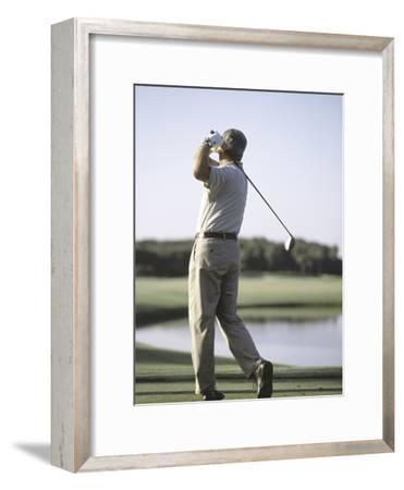 Rear View of a Senior Man Swinging a Golf Club