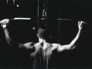 Rear View of a Young Man Exercise on a Lateral Pull-Down Weight Machine