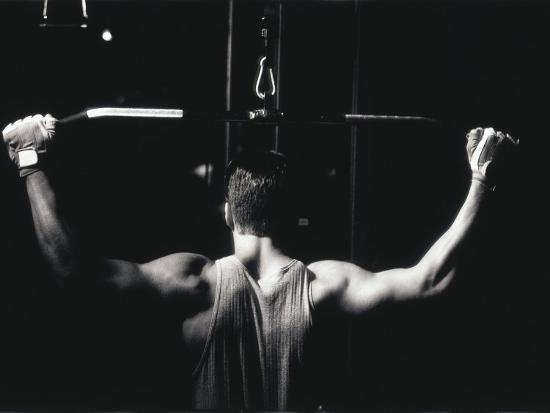 Rear View of a Young Man Exercise on a Lateral Pull-Down Weight Machine--Photographic Print