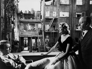 REAR WINDOW, 1954 directed byALFRED HITCHCOCK On the set, Grace Kelly between James Stewart and Alf