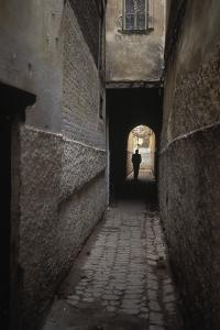 Silhouette of a Man Walking Through an Archway in Fez, Morocco by Rebecca Hale