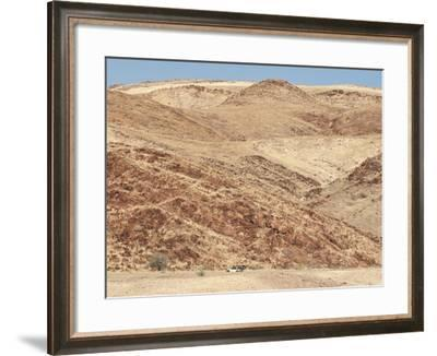 Red Rocky Landscape with Jeep in Distance, Purros Conservancy Wilderness, Kaokoland, Namibia-Kim Walker-Framed Photographic Print
