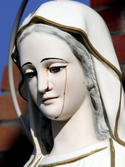 Red Stains are Seen Running from the Left Eye of a Statue of the Virgin Mary--Photographic Print