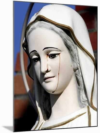 Red Stains are Seen Running from the Left Eye of a Statue of the Virgin Mary--Mounted Photographic Print