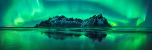 Reflection of Aurora Borealis in the sea with Vestrahorn mountains in center, Stokksnes Beach, S...
