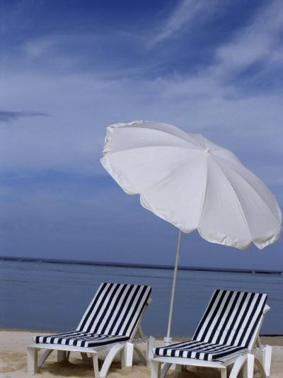 Relaxing Beach Chairs and Umbrella Await Customers-Paul Sutherland-Photographic Print