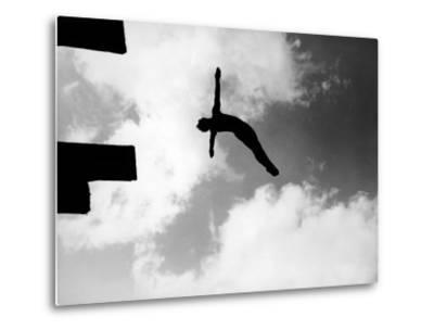 Excellent of Man Silhouetted Against Sky Doing Back Dive Off High Board