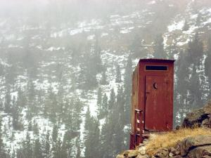Outhouse Perches on a Hillside by Rex Stucky