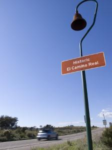 Historic el Camino Real Marker on Highway 101 and Car Whizzing Past, California by Rich Reid