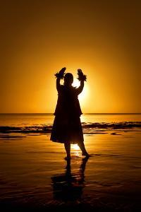 A Hula Dancer in Silhouette Along the Shoreline at Low Tide on Molokai Island by Richard A. Cooke III