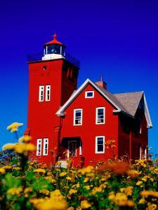Bright Red Two Harbors Lighthouse with Flowers in Foreground, Lake Superior, Two Harbours, USA by Richard Cummins