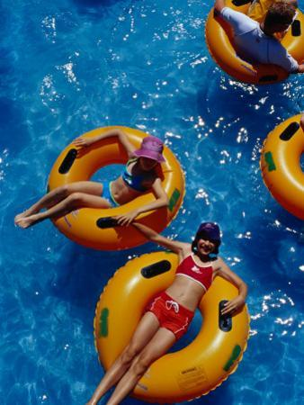 Young Girls Floating in Rubber Rings in Swimming Pool