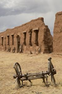 Old Wagon Wheels with Remnants of Fort Union Behind by Richard Maschmeyer