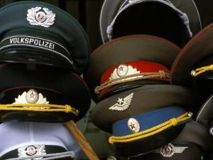 A Pile of Communist Era Army and Police Hats for Sale as Souvenirs, Mitte, Berlin, Germany by Richard Nebesky