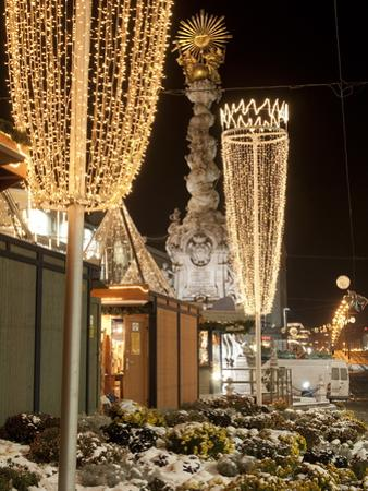 Snow-Covered Flowers, Christmas Decorations and Baroque Trinity Column at Christmas Market, Austria