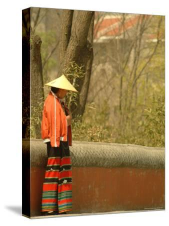 A Chinese Woman in a Straw Hat and Colorful Pants