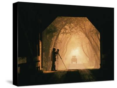 A Photographer Sets up His Camera in a Covered Bridge