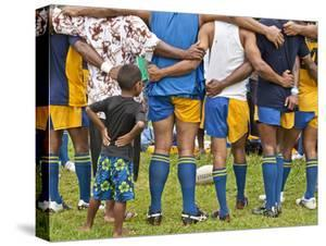 A Rugby Team in Huddle with a Child Watching Between Adults by Richard Nowitz