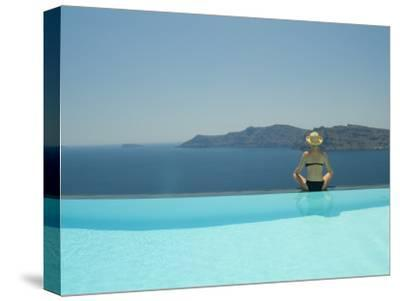 A Woman at the Edge of an Infinity Pool Overlooking the Aegean Sea
