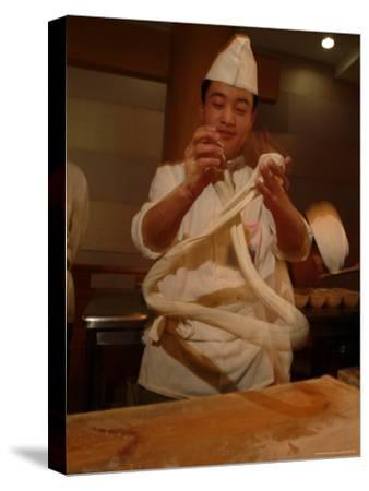 Chef Twirls Dough as He Makes Fresh Noodles in a Restaurant