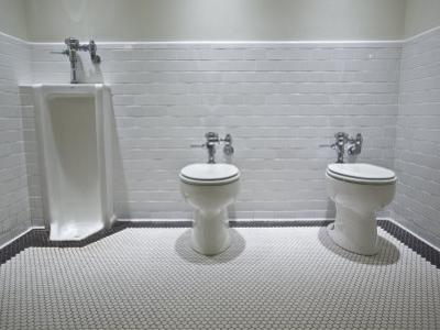 Marfa, Texas.White Tiled Men's Restroom with Two Toilets and One Urinal