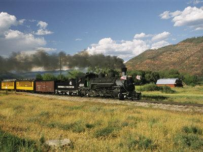 Old Locomotive with Billowing Black Smoke in Hilly Countryside