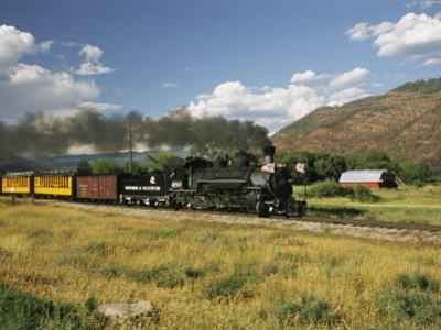 Old Locomotive with Billowing Black Smoke in Hilly Countryside by Richard Nowitz