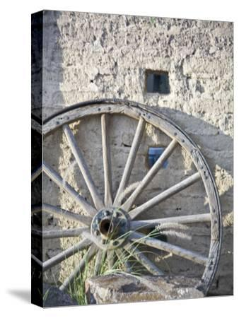 Texas, Western Themed Brewster County. Wagon Wheel Against White Washed Adobe Wall