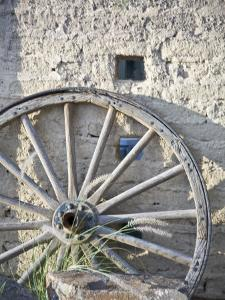Texas, Western Themed Brewster County. Wagon Wheel Against White Washed Adobe Wall by Richard Nowitz