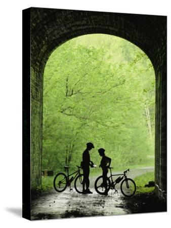 Two Silhouetted Cyclists Stop in a Tunnel on a Bike Trail