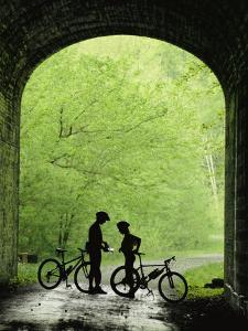 Two Silhouetted Cyclists Stop in a Tunnel on a Bike Trail by Richard Nowitz