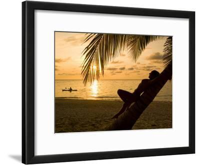 Woman Resting on a Palm Tree at Sunset, Sunset over the Caribbean Sea