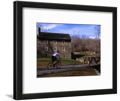 Man Cycling Past Building in Rock Creek Park, Washington Dc, USA