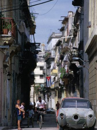 Woman with Baby, Man on Bicycle and Old Car in a Narrow Street Lined with Houses, Havana, Cuba