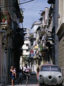 Woman with Baby, Man on Bicycle and Old Car in a Narrow Street Lined with Houses, Havana, Cuba by Rick Gerharter