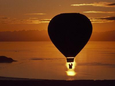 Riding in a Hot Air Balloon over Water at Sunset-Chris Johns-Photographic Print