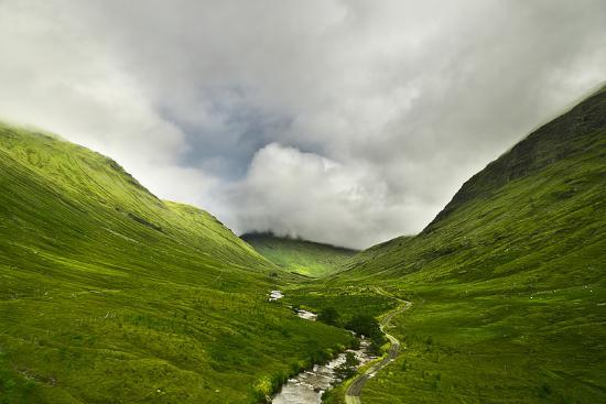 River Flowing through a Valley in the Scottish Highlands, the Mountains are Covered in Clouds-unkreatives-Photographic Print